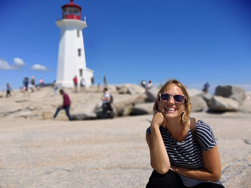 Woman smiling in front of lighthouse