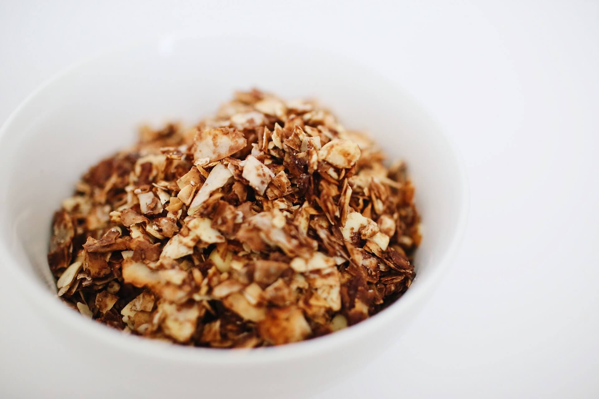 White bowl filled with breakfast granola with a white background