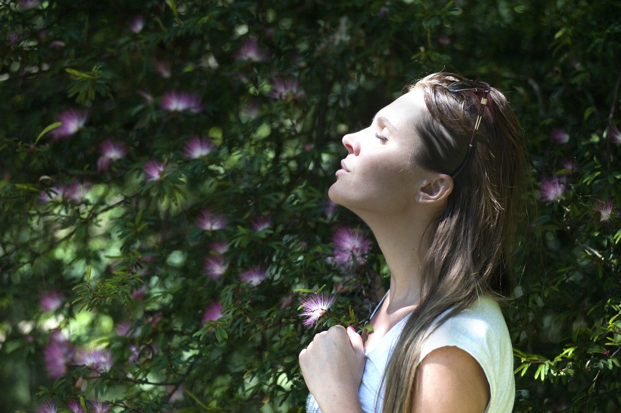 Woman taking a deep, calm breath with eyes closed