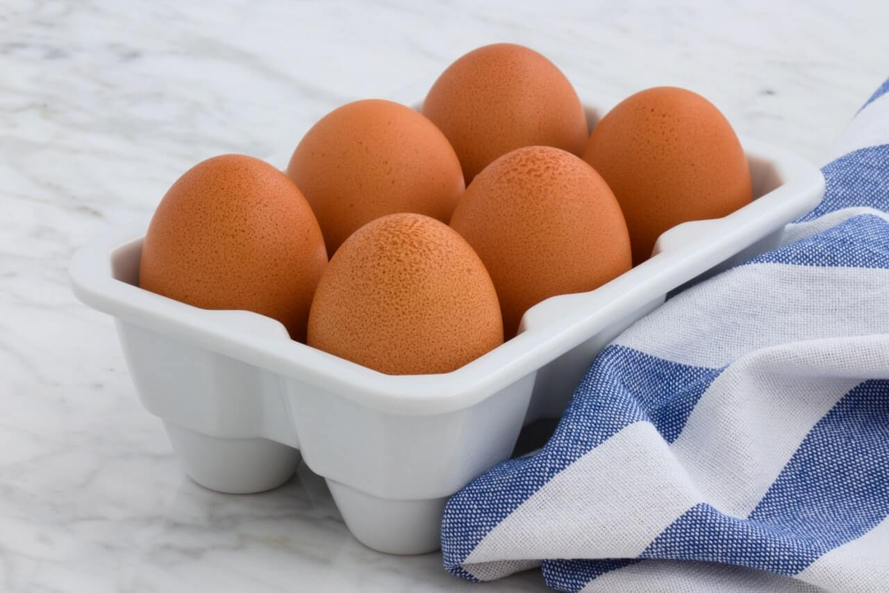 Six brown eggs in a container on a counter