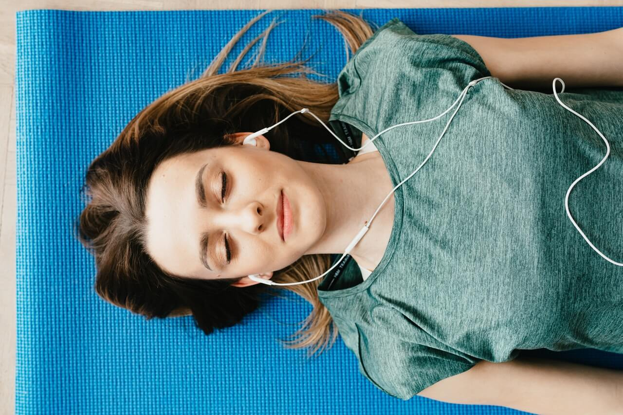 Girl with eyes closed lying on a yoga mat, listening to a guided meditation on headphones