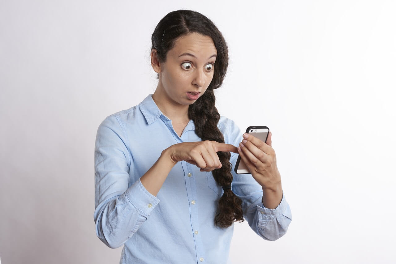 Surprised woman checking digital balance on phone
