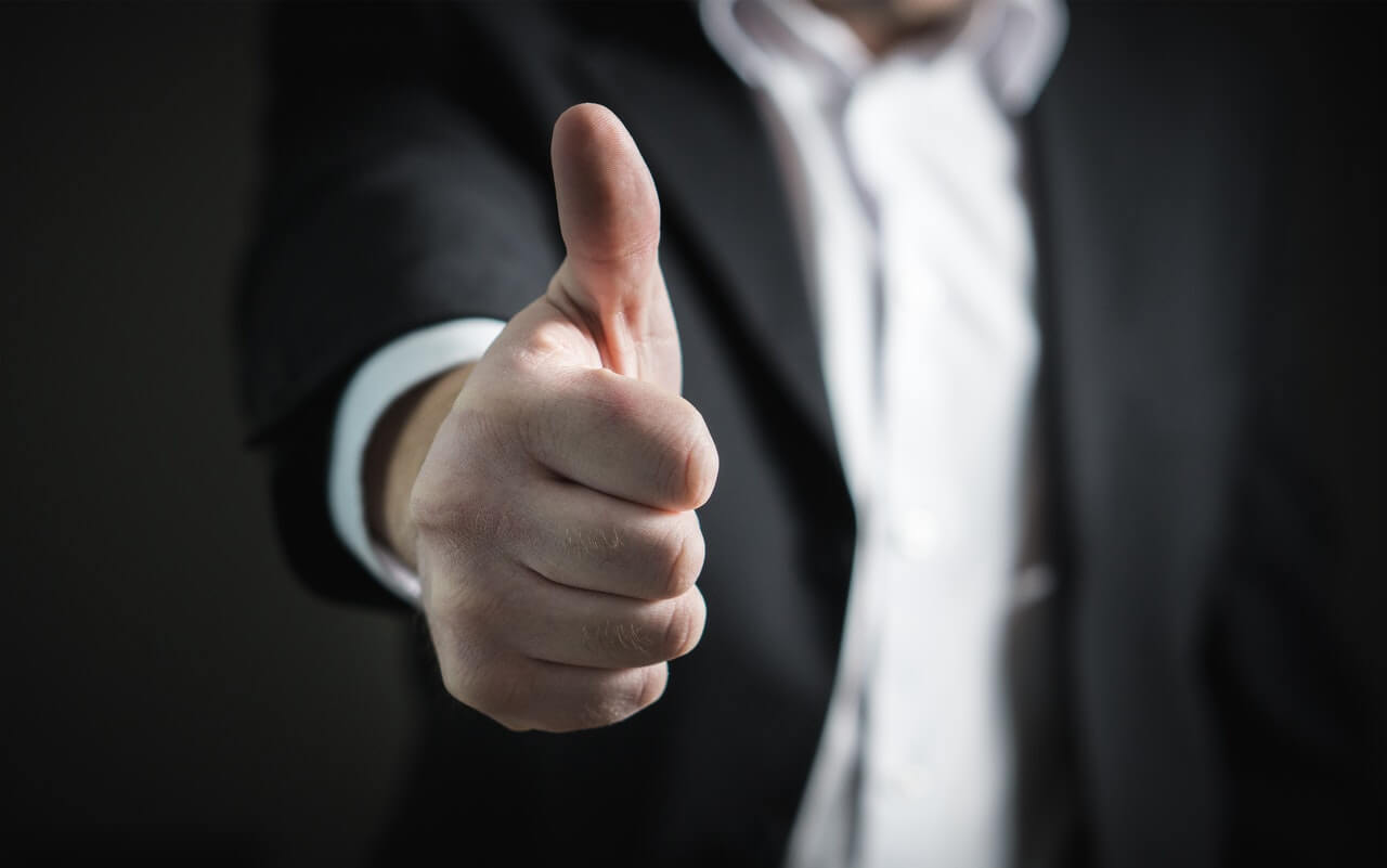 Man in suit giving thumbs up saying yes
