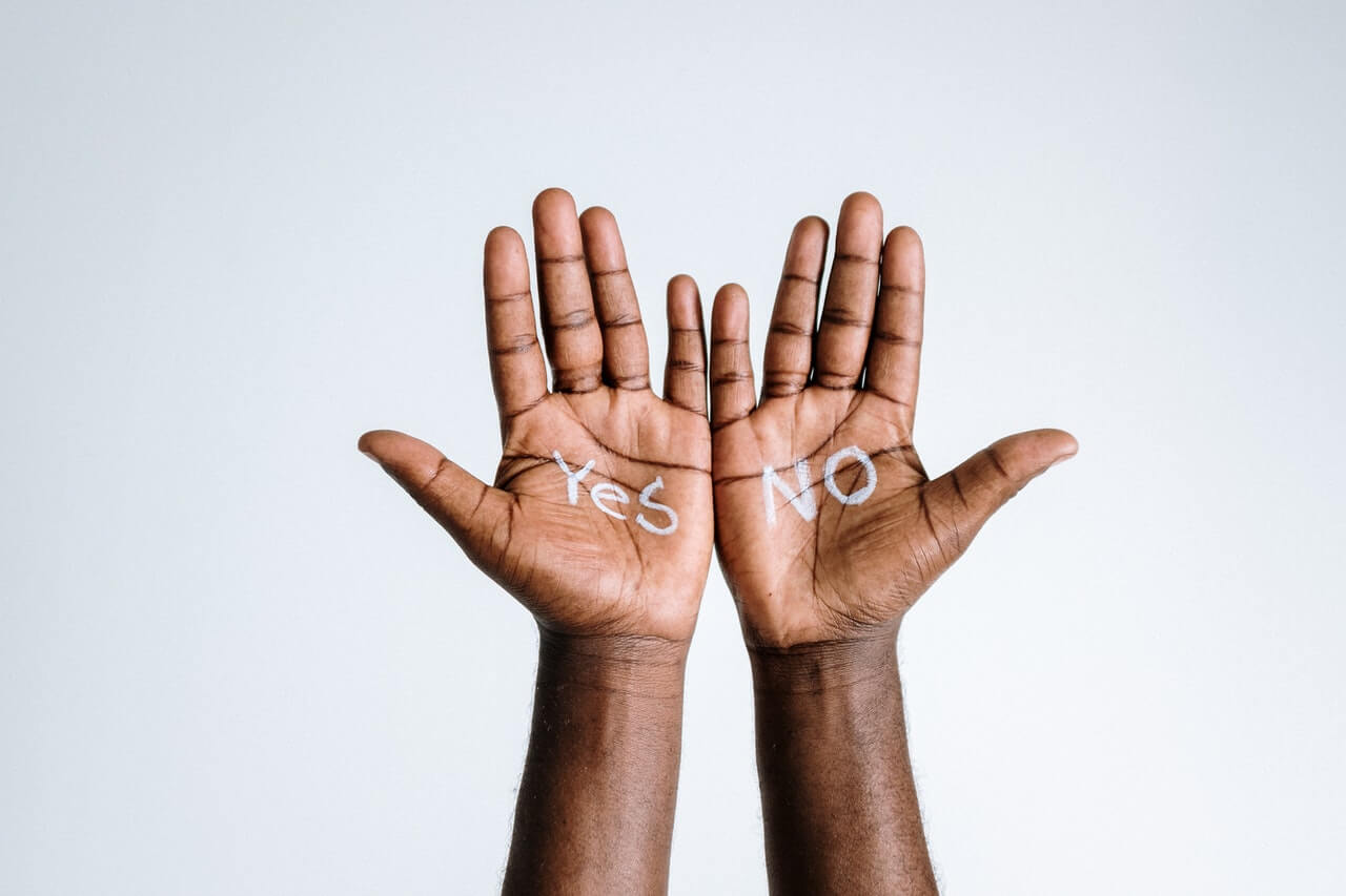 2 hands with Yes and NO written on each