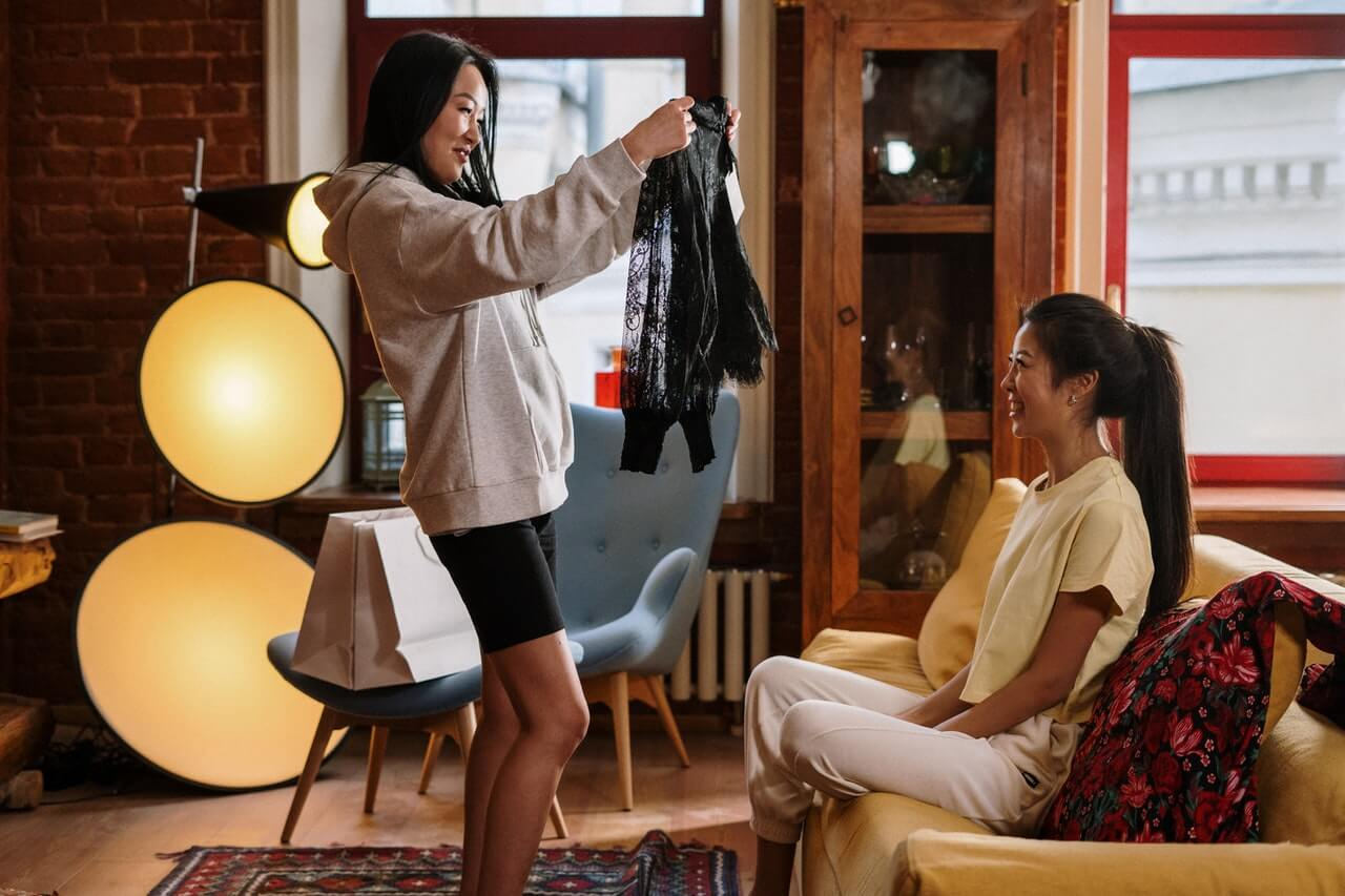 Girl standing in living-room holding up a black shirt in front of her friend, doing a clothes swap