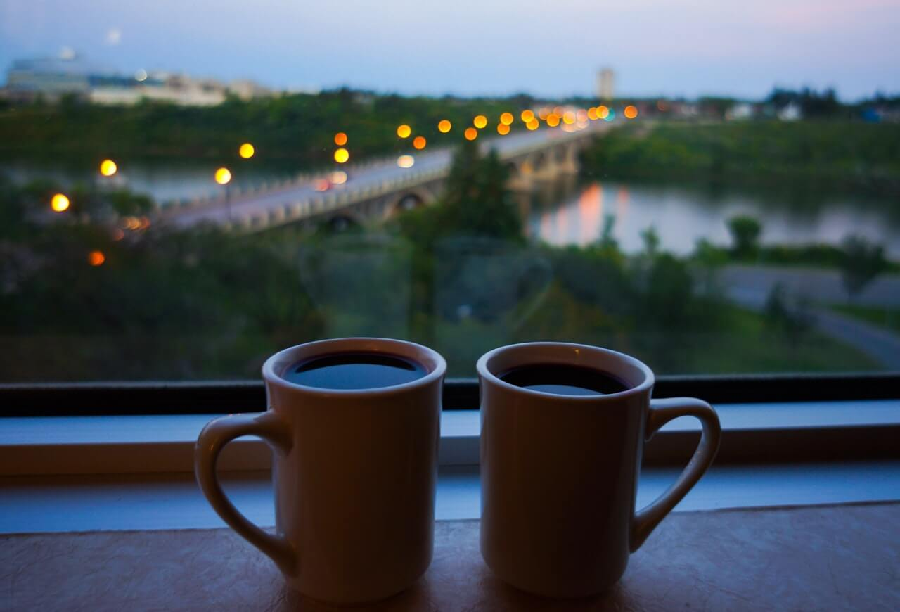 Coffee mugs sitting by window with a view of a bridge