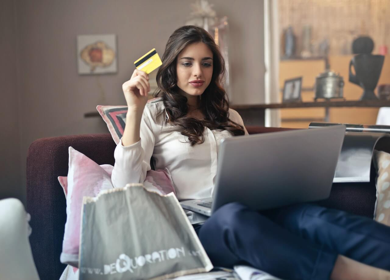 Woman holding gift card while shopping online