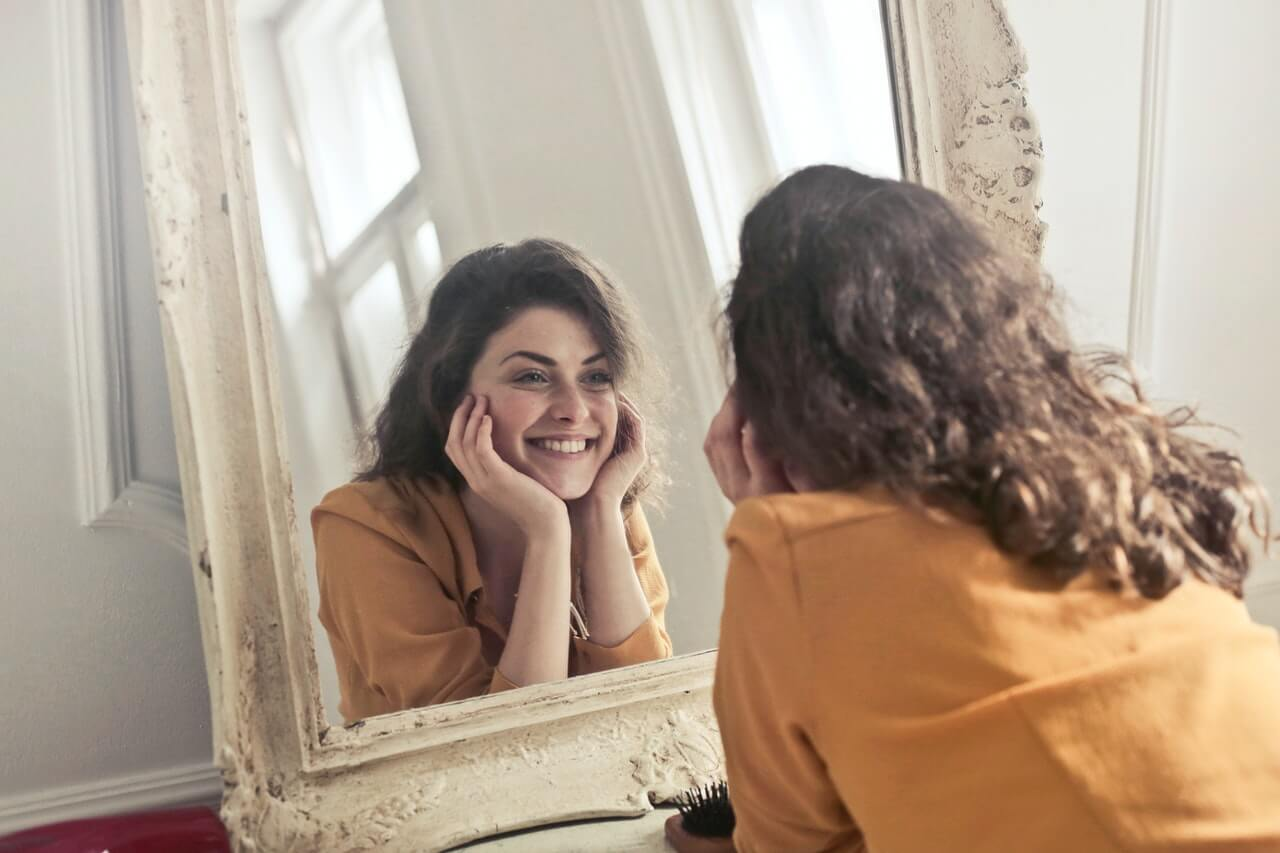 Happy woman smiling at herself in the mirror