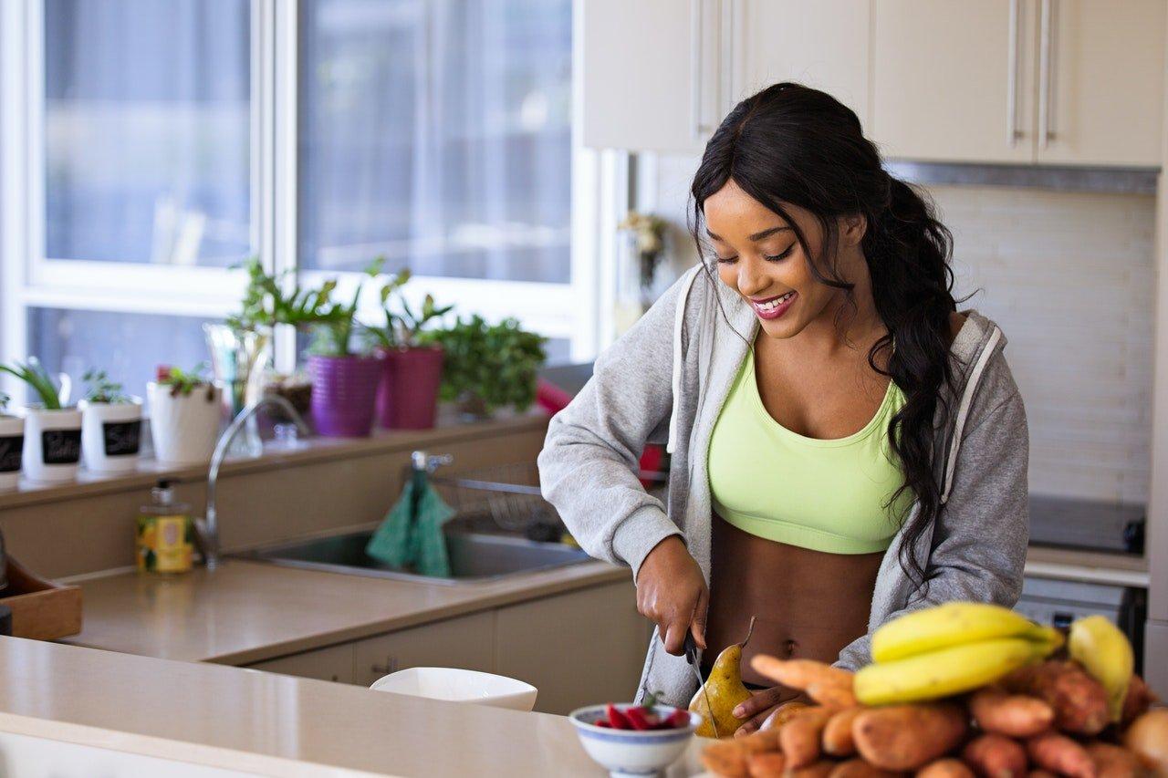 Woman cutting fruit preparing healthy morning breakfast
