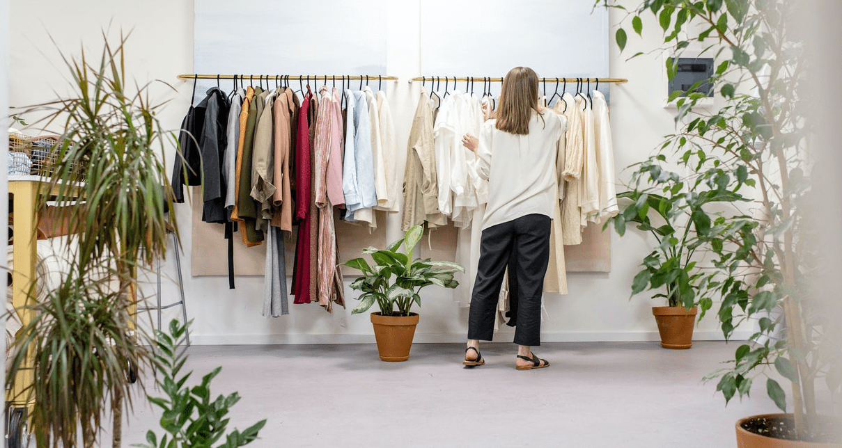 Woman standing in front of a clothes rail with clothes organised by colour