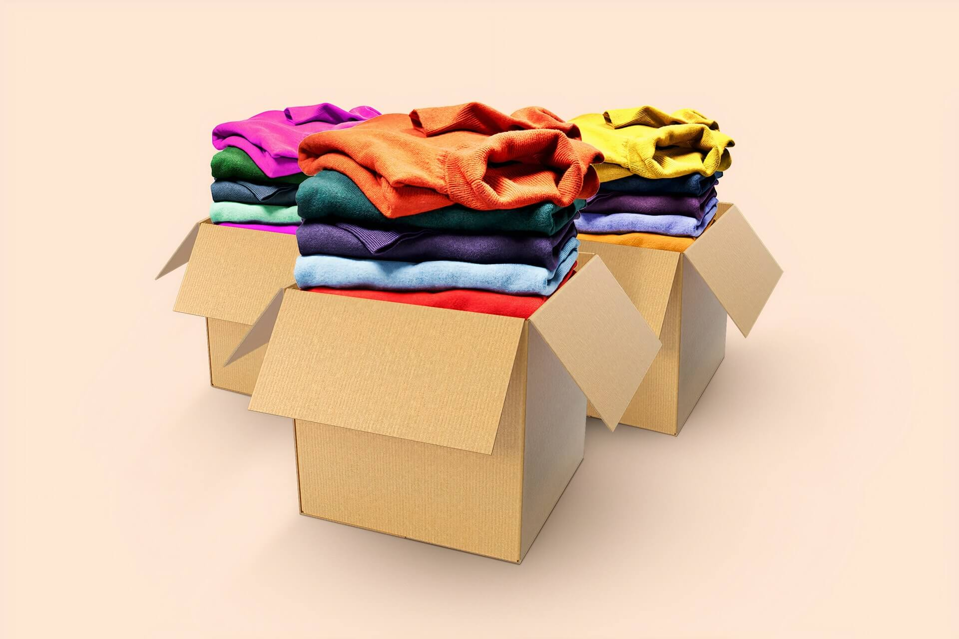 3 cardboard boxes with piles of folded clothes in each