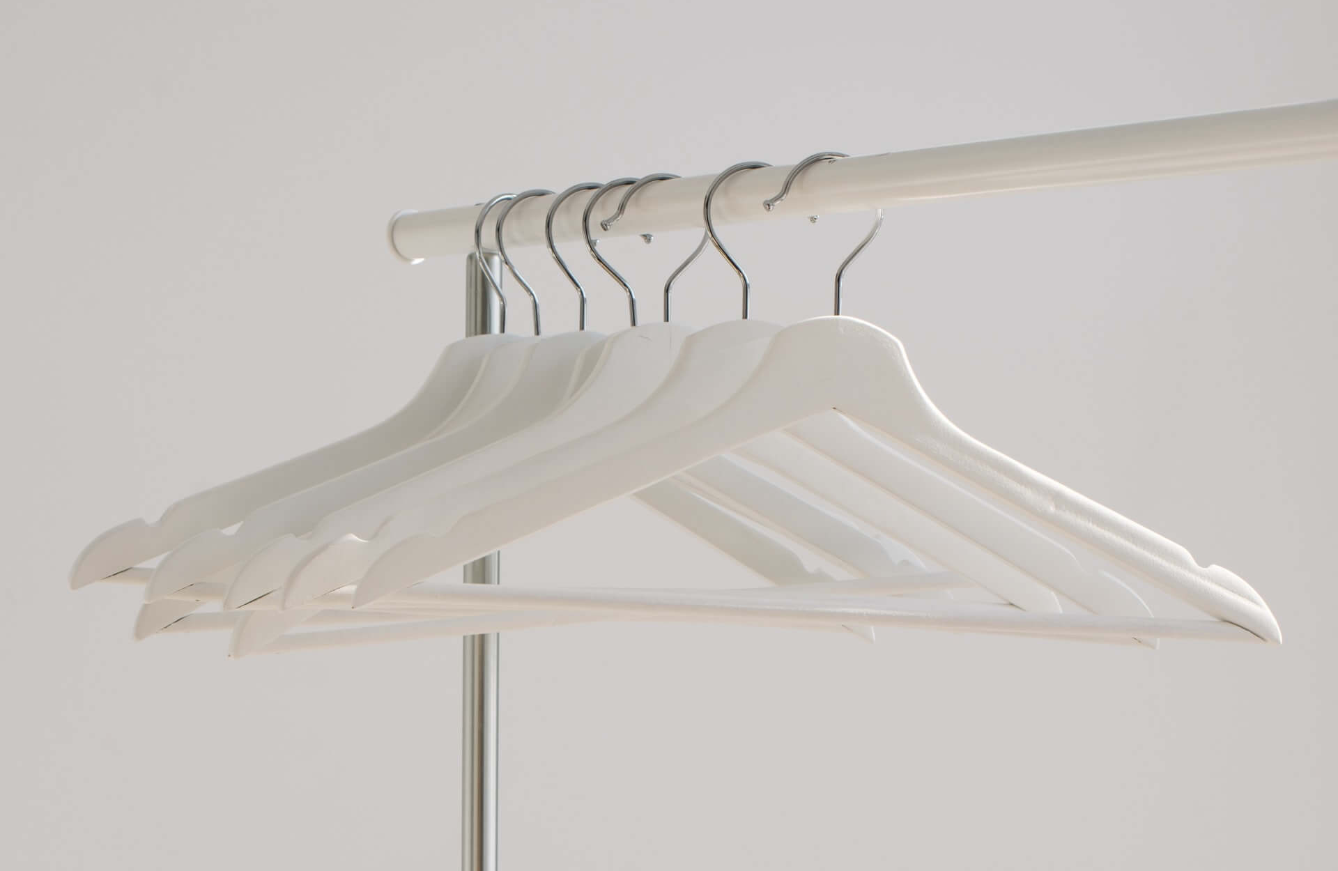 white wooden hangers on a clothes rail