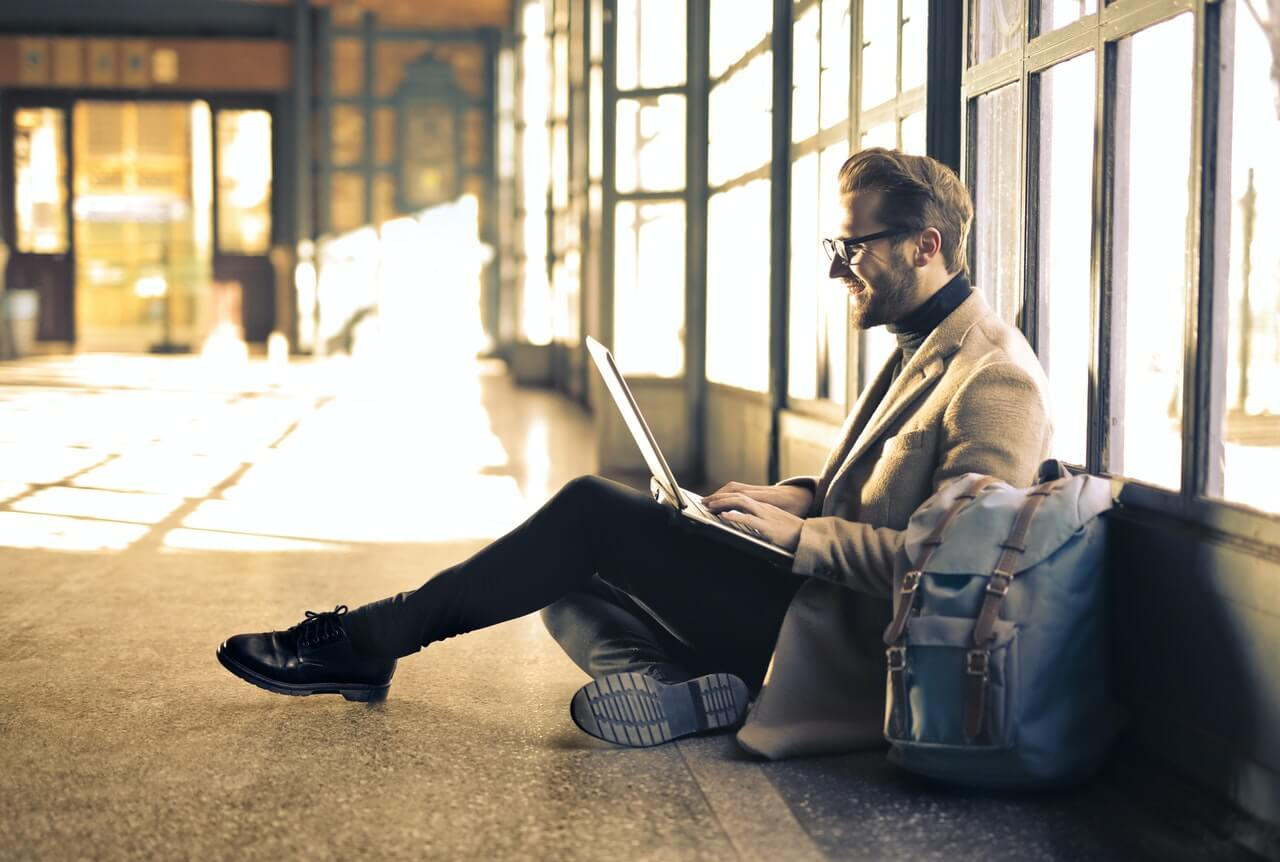 Man sitting on floor looking at online content on laptop