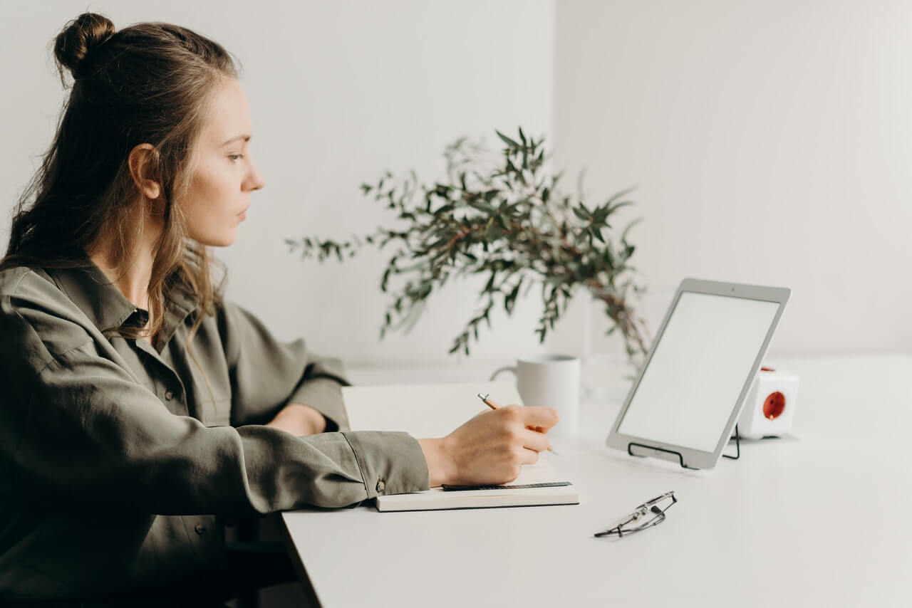 Woman sitting at desk with book and tablet