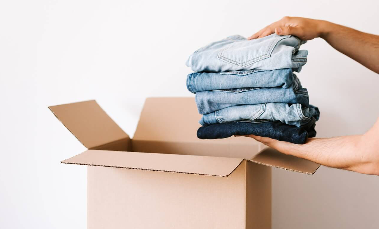 Hands putting a folded pile of jeans in a cardboard box to help declutter a wardrobe