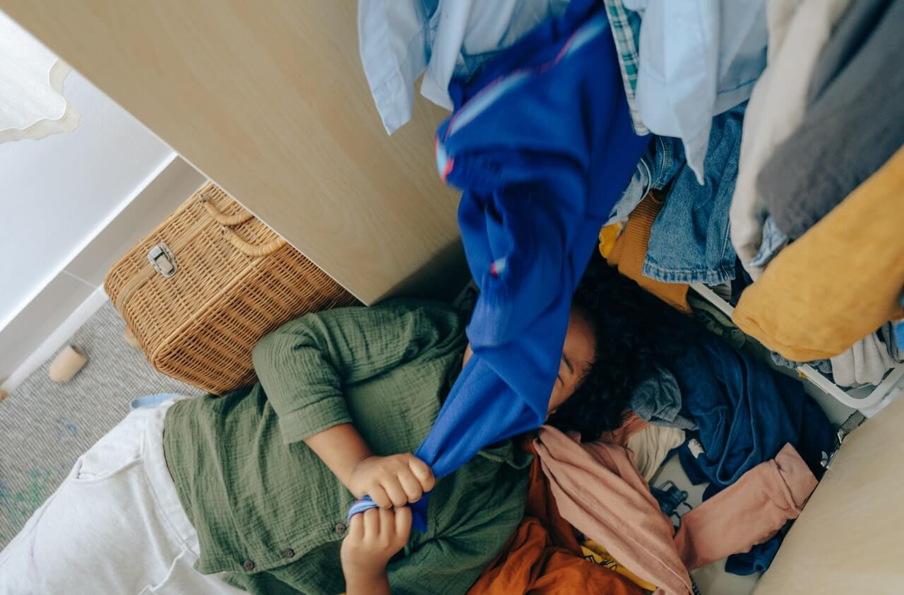 Woman lying on the floor with clothes from wardrobe all over her