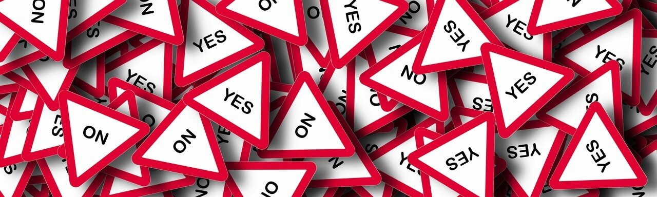 a pile of triangular signs that say yes and no